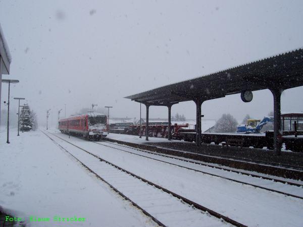 Um 10:07 Uhr verschwindet auch die RB nach Marburg im Schneetreiben. Rechts steht der Güterzug der Siegener Kreisbahn bereit für die Fahrt nach Kreuztal. Sobald die RB nach Siegen Lützel verlassen hat, kann er in Richtung Hilchenbach abfahren.
