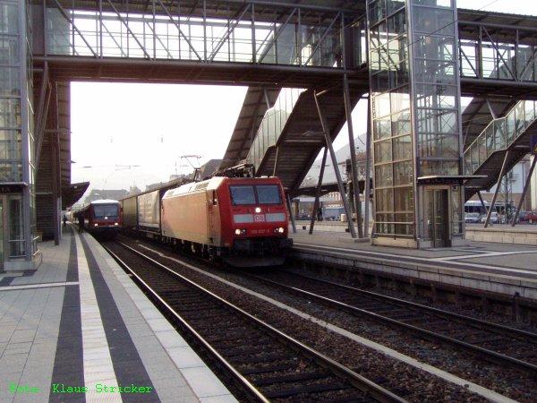 185 037 fährt mit einem Güterzug durch während links ein 628 auf Fahrgäste wartet.